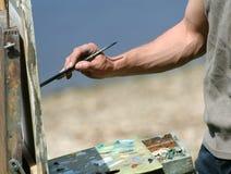 Hand des Künstlers mit einem Pinsel Lizenzfreie Stockfotos