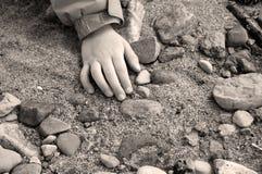Hand des Kindes auf Sand und Steinen Lizenzfreie Stockfotos