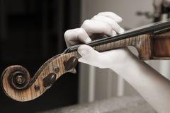 Hand des Kindes, die eine Violine palying ist Lizenzfreie Stockfotografie