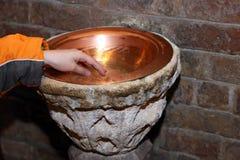 Hand des Kindes und des alten Weihwasserbeckens in einem kupfernen Vase Stockfotografie