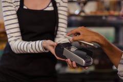 Hand des Kunden zahlend durch Bankkarteleser mit seinem Smartphone stockbild