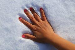 Hand des Mädchens auf Schnee Stockfoto