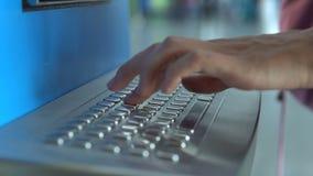 Hand des Mädchens ihren Namen auf Flughafenabfertigungs-Kiosktastatur füllend, um eine Karte im Flughafenabfertigungsgebäude zu e stock video footage