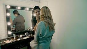 Hand des Make-upmeisters, malende Lippen des jungen schönen Modells Make-up laufend stock video