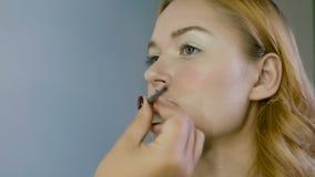 Hand des Make-upmeisters, malende Lippen des jungen schönen Modells Make-up laufend stock footage
