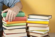 Hand des Mannes auf Stapel bunten Büchern Scheren und Bleistifte auf dem Hintergrund des Kraftpapiers Lizenzfreie Stockfotos
