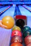 Hand des Mannes, der Kugel für Throw im Bowlingspiel nimmt lizenzfreies stockbild