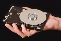 Hand des Mannes, die ein Festplattenlaufwerk auseinandergenommen anhält stockfotografie