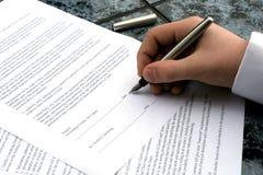 Hand des Mannes, die eine Feder schreibt eine Unterzeichnung anhält Stockfoto