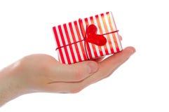 Hand des Mannes, die einen freundlich verzierten Geschenkkasten anhält Lizenzfreie Stockfotografie