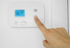 Hand des Mannes, die Kühlertemperatur justiert Lizenzfreie Stockbilder