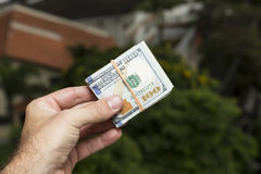 Hand des Mannes Dollarscheine vor einer Stadtlandschaft halten Lizenzfreie Stockbilder