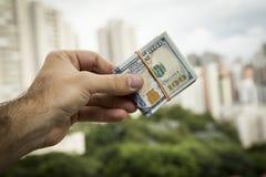 Hand des Mannes Dollarscheine vor einer Stadtlandschaft halten Lizenzfreies Stockbild