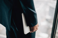 Hand des Mannes in holdning Laptop des Gesellschaftsanzugs stockbild