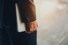 Hand des Mannes in holdning Laptop des Gesellschaftsanzugs stockfoto