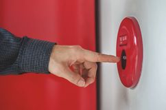 Hand des Mannes ist Pressefeuermelderschalter auf der weißen Wand als Hintergrund für Notfall am Gebäude lizenzfreie stockbilder