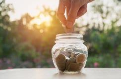 Hand des Mannes Münze und Tropfen in das Glas halten Finanz-stoc Lizenzfreie Stockfotografie