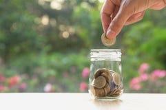 Hand des Mannes Münze und Tropfen in das Glas halten Finanz-stoc Stockfoto