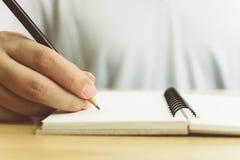 Hand des Mannes mit Bleistiftschreiben auf Notizbuch Lizenzfreie Stockfotografie