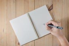 Hand des Manngebrauchs-Bleistiftschreibens auf weißem Notizbuch auf Holztisch Lizenzfreie Stockfotos