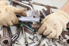 Hand des Mechanikermaßes das Teil mit einem Tasterzirkel in der Werkstatt Lizenzfreies Stockfoto
