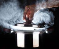 Hand des offenen heißen Stromtopfes des Chefs mit schöner Studiobeleuchtung Stockfoto