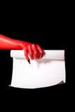 Hand des roten Teufels mit den schwarzen Nägeln, die Papierrolle halten Lizenzfreies Stockfoto