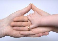 Hand des Schätzchens, welche die Hände der Muttergesellschaft anhält Lizenzfreie Stockbilder