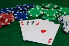 Hand des Schürhakens, vier Asse und der Chips auf einem geglaubten grünen Hintergrund Weißer Hintergrund stockfotos