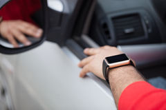 Hand des schwarzen Mannes die intelligente Uhr tragend, die im Auto sitzt stockbilder