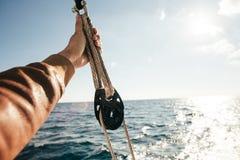 Hand des Seemanns hält auf einfangen Flaschenzug Stockbild