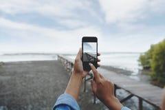Hand des selektiven Fokus unter Verwendung des intelligenten Telefons, das Landschaftsfoto macht Stockfotos