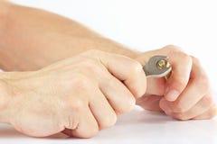Hand des Soldaten mit einem Schlüssel, zum der Nuss auf weißem Hintergrund festzuziehen Lizenzfreie Stockfotos