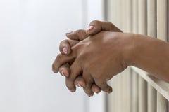 Hand des weiblichen Gefangenen auf weißen Eisenzellstangen lizenzfreie stockfotografie