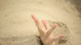 Hand desperately waving, sinking in quicksand, trapped tourist in desert, danger. Stock footage stock video