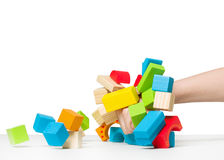 Hand destroying house made of color wooden blocks копи Royalty Free Stock Images