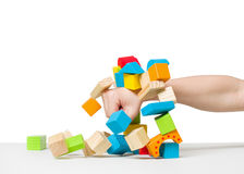 Hand destroying house made of color wooden blocks Stock Photo
