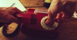 Hand dial a number on a old retro rotary phone. Dolly shot stock video footage