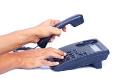 Hand dialing or picking up telephone. Hand dialing or picking up telephone on white background Stock Image