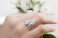 Hand with diamond ring. Diamond ring on beauty hand and white flower backgorund. Shinning diamond stock photography