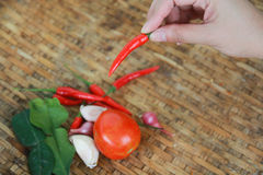 Hand die één rode Spaanse peperpeper over oude mandewerkachtergrond houden Stock Foto
