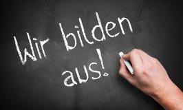 Hand die 'wij leiden mensen op schrijven! 'in het Duits stock afbeelding