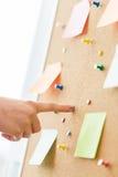 Hand die aan cork raad met stickers en spelden richten Stock Fotografie