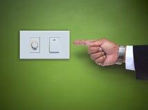 Hand die aan schakelaar ofelectric toestel richten op groene muur Stock Foto's