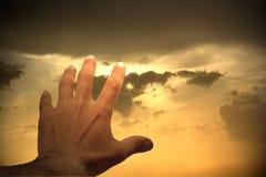Hand die aan zonsonderganghemel bereiken Stock Foto's