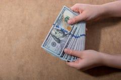 Hand die Amerikaanse dollar op houten achtergrond houden stock afbeelding
