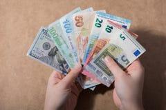 Hand, die amerikanischen Dollar auf hölzernem Hintergrund hält lizenzfreie stockfotografie