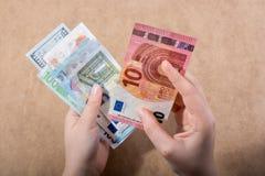 Hand, die amerikanischen Dollar auf hölzernem Hintergrund hält lizenzfreie stockfotos