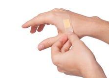 Hand, die anhaftenden Verband setzt Stockbilder