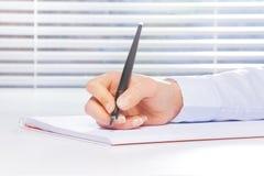 Hand, die Anmerkungen auf dem Ring-gehenden Notizbuch macht Lizenzfreie Stockfotos